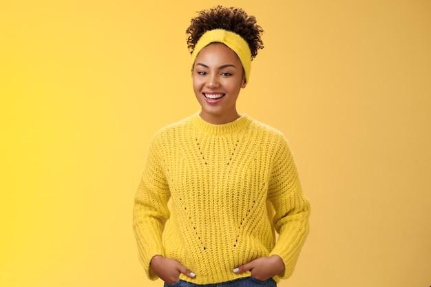 Amigável descontraído jovem afro-americano linda garota headband testa no suéter segurar as mãos nos bolsos sorrindo amplamente se divertir falando uma comunicação interessante, parede amarela de pé.