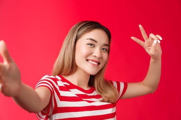 Amigável extrovertido linda menina asiática loira curto penteado estender o braço segurar a câmera do smartphone inclinar a cabeça ...
