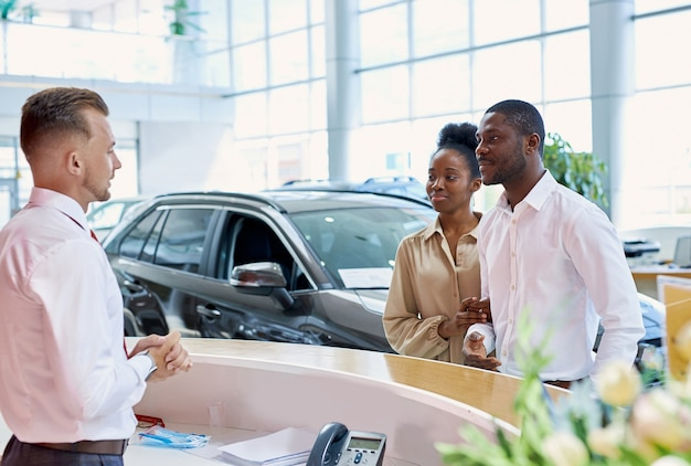 Amigável gerente caucasiana cumprimentando clientes no salão do carro