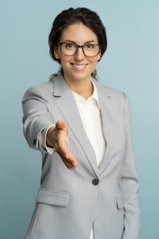 Amigável, hospitaleira alegre mulher de negócios ou trabalhador de escritório usa blazer dando a mão para um aperto de mão