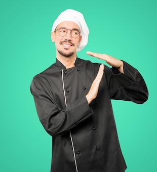 Amigável jovem chef fazendo um gesto de tempo com as mãos