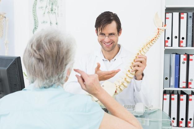 Amigável médico explicando a coluna para um paciente sênior