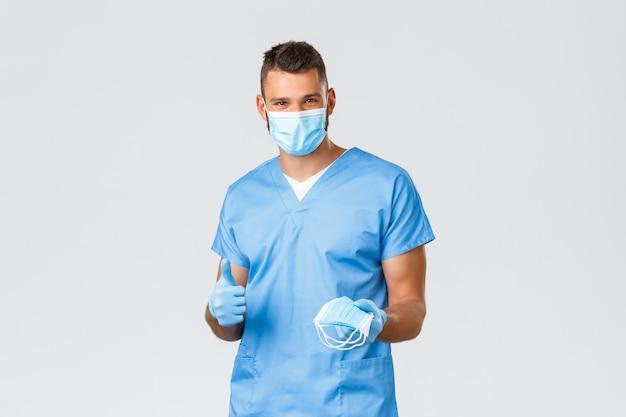 Amigável médico sorridente, enfermeiro em equipamentos de proteção individual e avental, polegar recomenda recomendar máscara médica