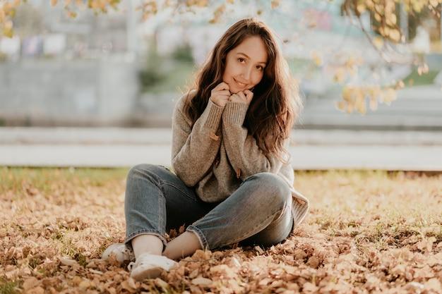 Amigável mulher morena com cabelos cacheados longos no suéter de lã aconchegante, sentada no chão com folhas douradas, temporada de outono