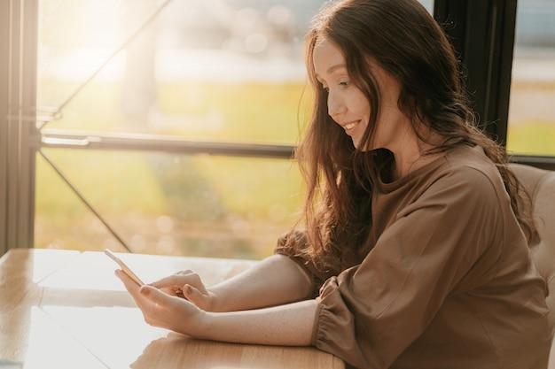 Amigável mulher morena com cabelos longos encaracolados, sentado à janela no café com o celular nas mãos