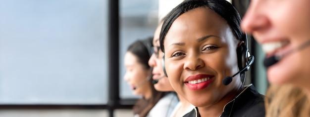 Amigável mulher negra usando fone de ouvido microfone trabalhando em call center