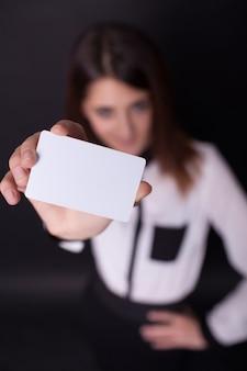 Amigável mulher segurando um cartão e sorrindo