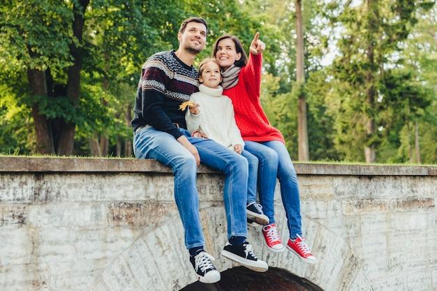 Amigável pai, mãe e filha sentar na ponte de pedra, olhar de cima