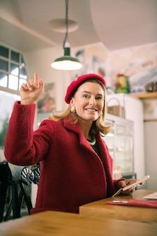 Amigo acenando. mulher bonita e elegante usando um casaco vermelho acenando para a amiga vê-lo no refeitório