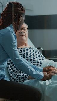 Amigo afro-americano visitando paciente idoso na enfermaria do hospital