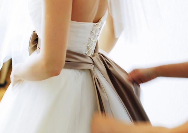 Amigo amarra um laço no vestido da noiva