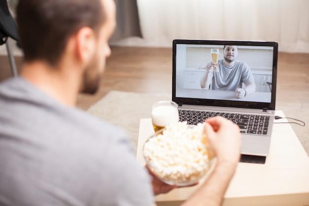 Amigo bebendo cerveja e comendo pipoca durante uma videochamada durante a quarentena.