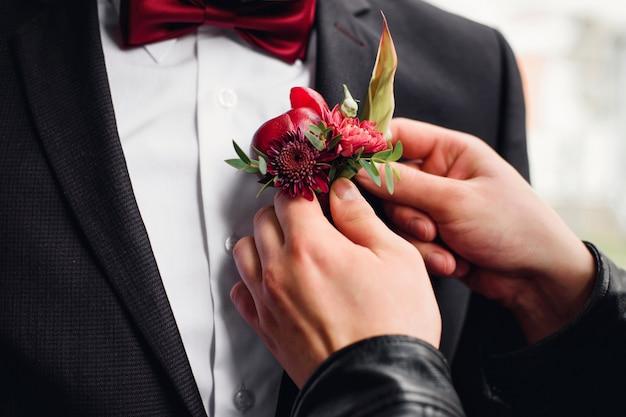 Amigo coloca uma flor na lapela no terno do noivo
