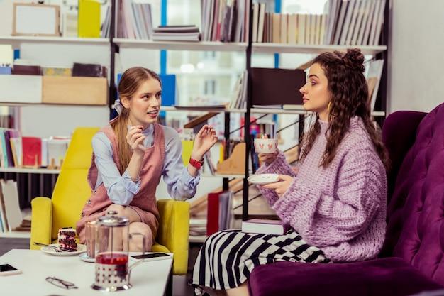 Amigo de cabelos escuros. amigas elegantes e bonitas visitando um café com sobremesas saborosas e várias coleções de livros