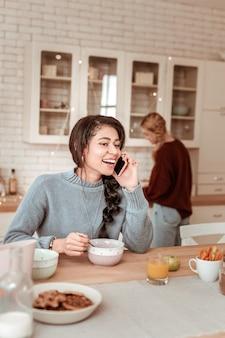 Amigo ficar para trás. jovem faladora com uma trança exuberante, conversando ativamente enquanto toma um café da manhã leve