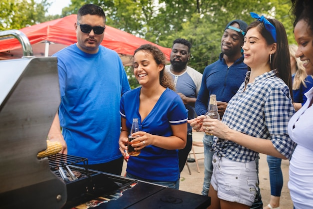 Amigo grelhando hambúrgueres em uma festa ao ar livre