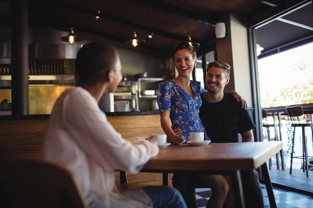 Amigo interagindo com casal feliz enquanto toma um café