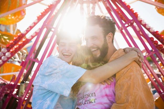 Amigos abraçando na luz solar no parque de diversões