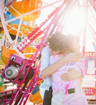 Amigos abraçando no parque de diversões na luz solar