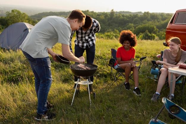 Amigos acampando juntos com churrasco completo