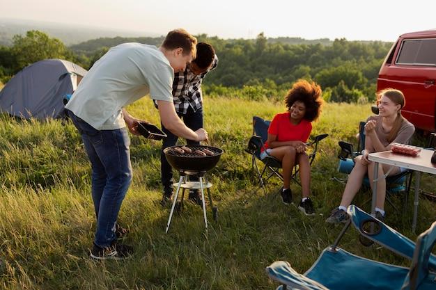 Amigos acampando juntos em cena completa