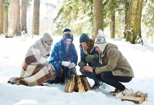 Amigos acampando na floresta de inverno