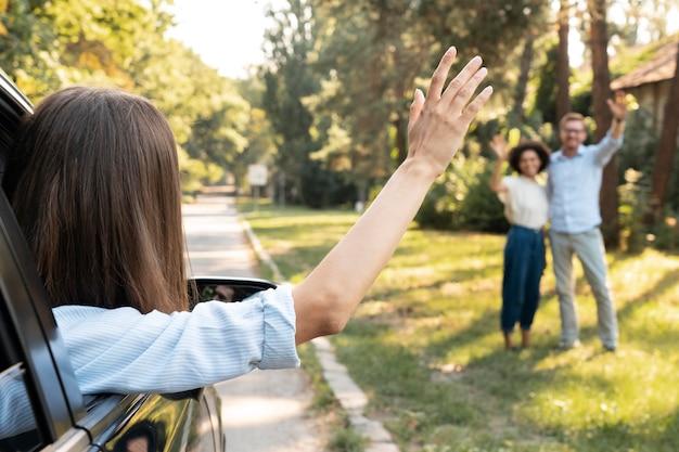 Amigos acenando um para o outro ao ar livre, do carro
