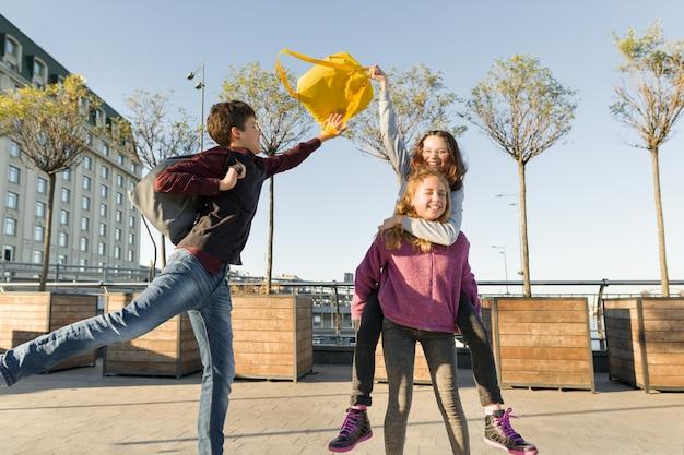 Amigos adolescentes estudantes com mochilas escolares, se divertindo no caminho da escola