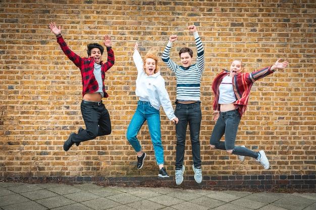 Amigos adolescentes felizes pulando na frente de uma parede