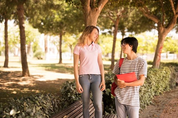 Amigos adolescentes multiétnicas, andando ao redor do parque