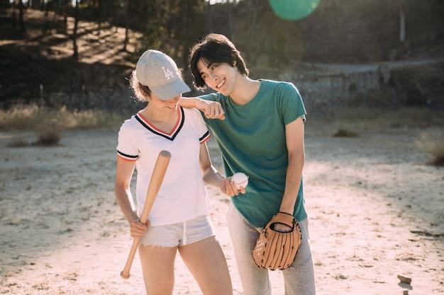 Amigos adolescentes multiétnicas, desfrutando de jogo de beisebol