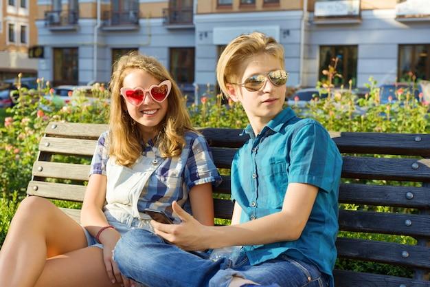 Amigos adolescentes, sentado no banco na cidade