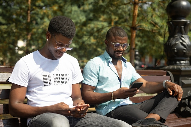 Amigos africanos em um banco de parque com telefones