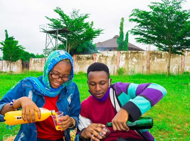 Amigos africanos felizes transformando a bebida em seu copo - conceito de amizade