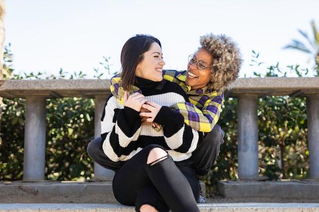 Amigos afro-americanos e caucasianos se abraçaram e felizes