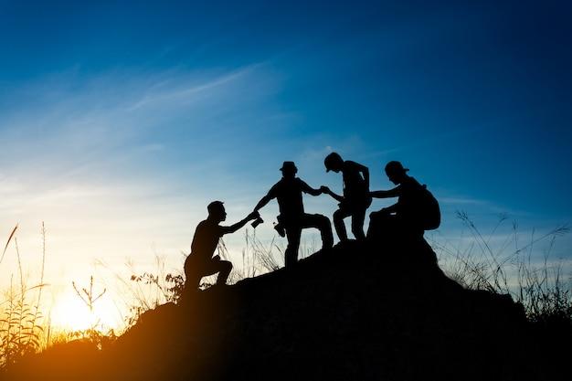 Amigos ajudando uns aos outros e com trabalho em equipe tentando alcançar o topo das montanhas