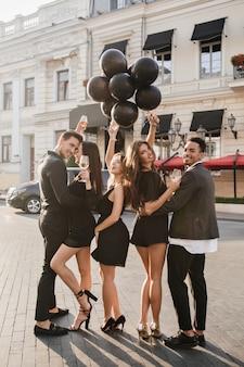 Amigos alegres bebendo champanhe em festa ao ar livre