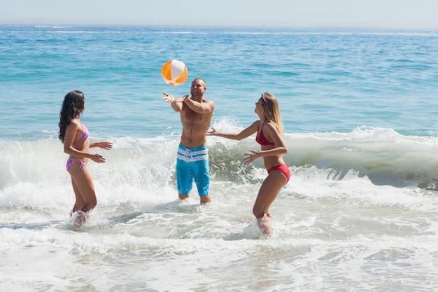 Amigos alegres brincando com uma bola de praia no mar