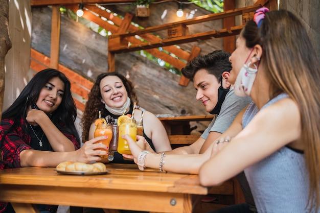 Amigos alegres brindando com um saudável suco de laranja em um bar.