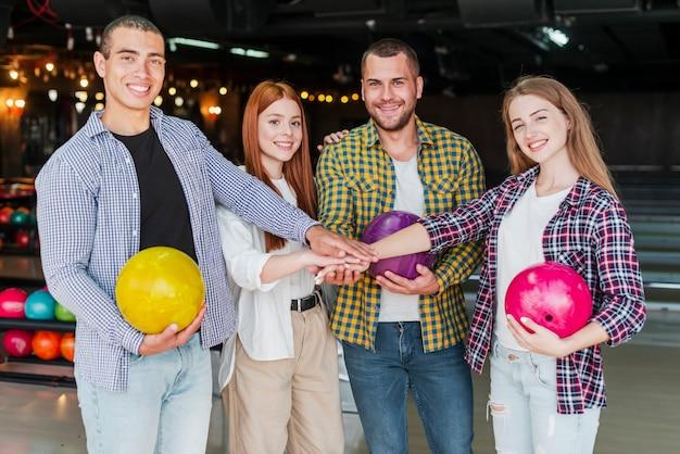 Amigos alegres com bolas de boliche em um clube de boliche