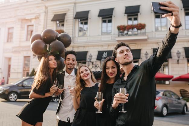 Amigos alegres com grandes sorrisos tirando fotos durante a celebração
