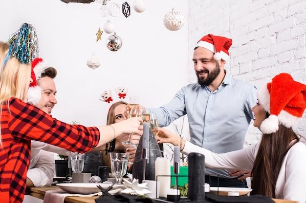 Amigos alegres da festa de natal a beber e a divertir-se