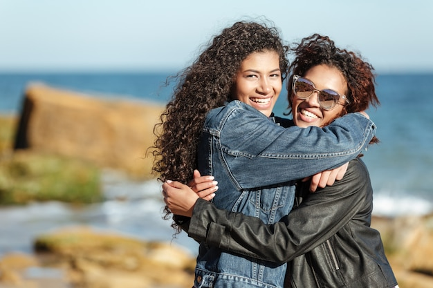Amigos alegres da mulher africana que andam ao ar livre na praia.