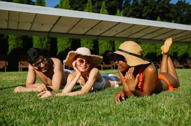 Amigos alegres descansam na grama perto da piscina