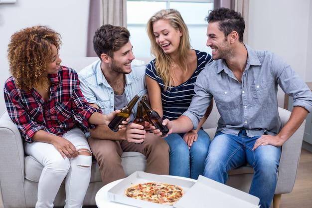 Amigos alegres, desfrutando de cerveja e pizza