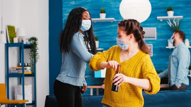 Amigos alegres e felizes tocando o cotovelo, mantendo o distanciamento social, cumprimentando-se usando máscara no rosto, evitando a propagação do coronavírus, segurando garrafas de cerveja na sala de estar