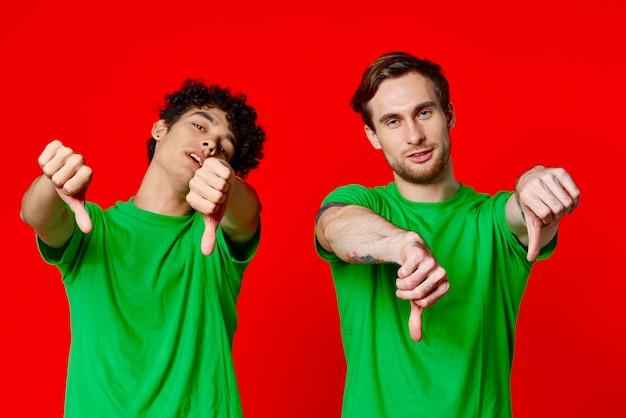 Amigos alegres em camisetas verdes gesticulando com as mãos isoladas no fundo