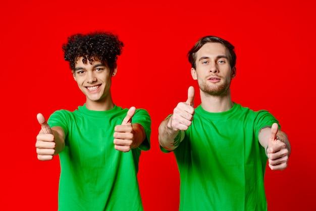 Amigos alegres em camisetas verdes gesticulando com fundo vermelho de emoções de mãos. foto de alta qualidade