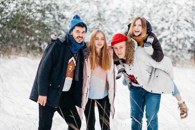 Amigos alegres em pé na floresta de inverno