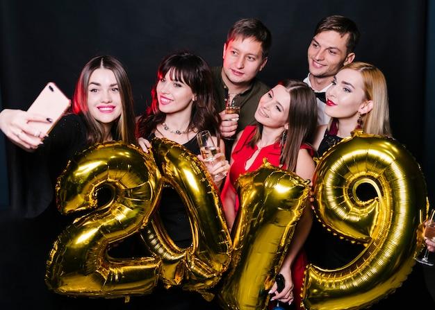 Amigos alegres, fazendo selfie com balões número 2019